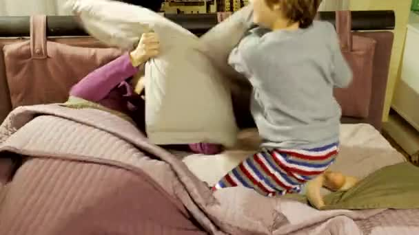 Mother and son having fun doing pillow fight in bed