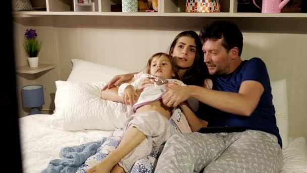 Happy family watching television in bed using remote control