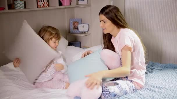 Sisters having fun in bed with pillows
