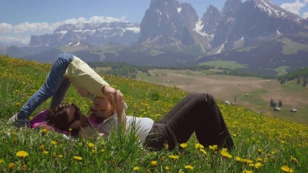 Woman playing with little daughter lying on grass with flowers in mountains