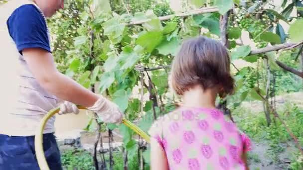 Happy kids gardening giving water to vegetables