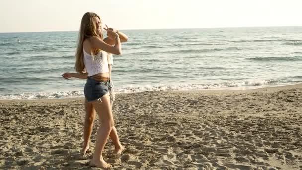 Happy cute girls dancing on the beach in summer having fun slow motion