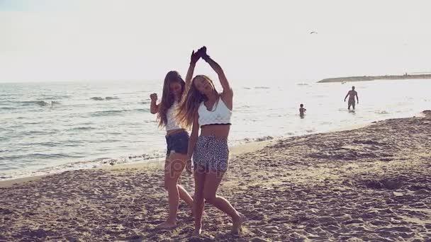 Happy cute girls dancing on the beach in summer having fun retro style