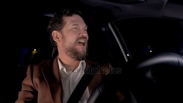 Felice delluomo di affari che conduce automobile canto di notte