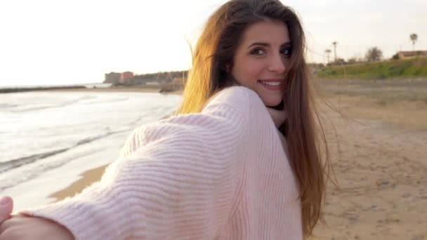 Nádherná žena s úsměvem držení rukou přítel chůze na pláž retro stylu