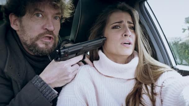 Criminal kidnapping woman in car pointing gun closeup film look