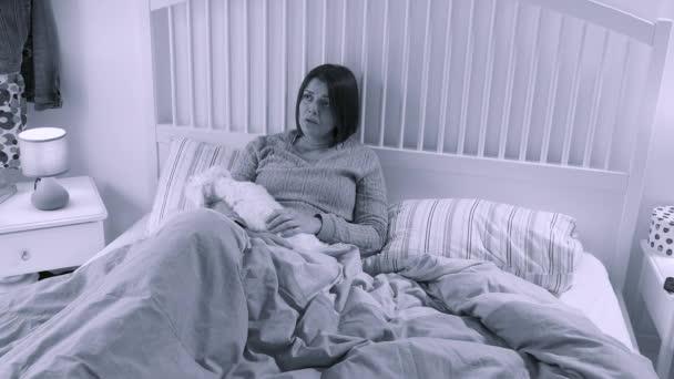 Traurige depressive Frau sitzt unglücklich im Bett