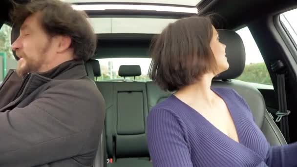 Happy couple entering car putting seat belt