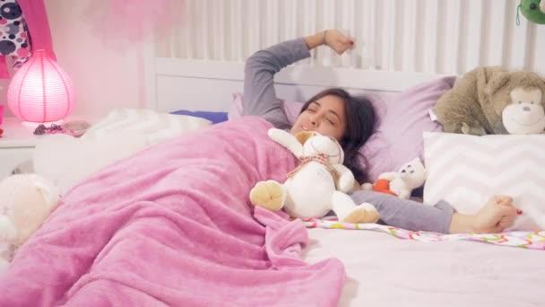 Mladá žena spát v posteli s hračka plyš probuzení v dopoledních hodinách
