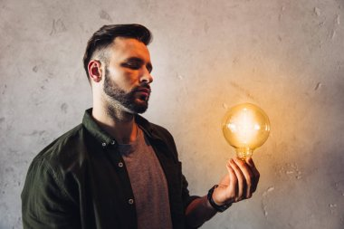 Serious bearded man holding illuminated light bulb while standing near grey wall stock vector