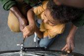 afro Atya és fiú kerékpár javítás