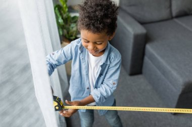 Adorable afro boy with measuring tape