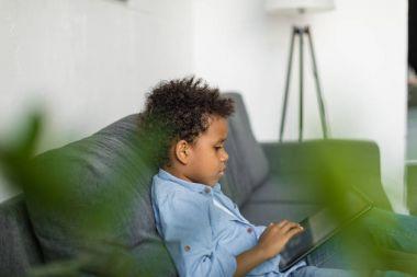 Thoughtful boy using digital tablet on sofa