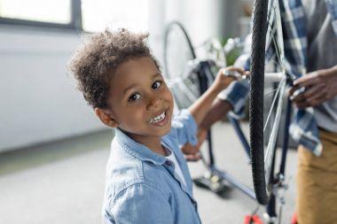 adorable afro boy repairing bicycle