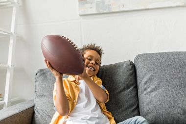 Afro boy with american football ball
