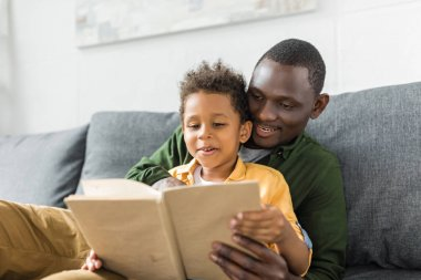 father and son reading book together