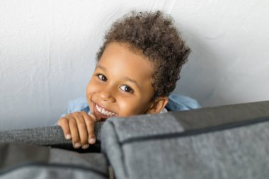 adorable afro boy hiding by sofa