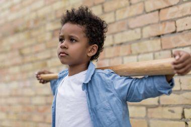 pensive afro boy with baseball bat