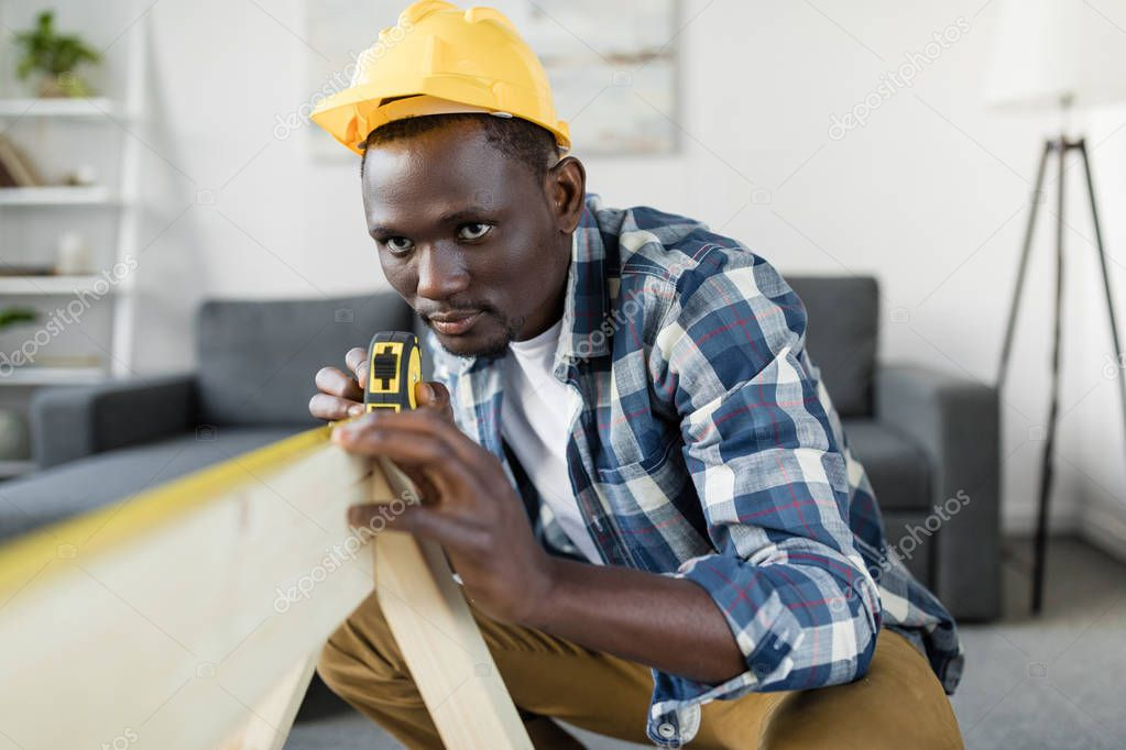 handsome afro builder with measuring tape