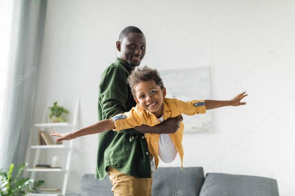Afro father and son playing at home