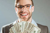 Young rich smiling businessman holding dollar bills isolated on grey