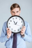 Photo Businessman in shirt holding clock in front of him isolated on grey