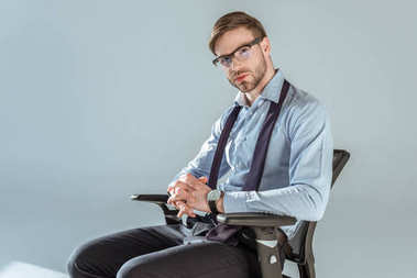 Young confident businessman sitting on chair with hands clenched,  isolated on grey