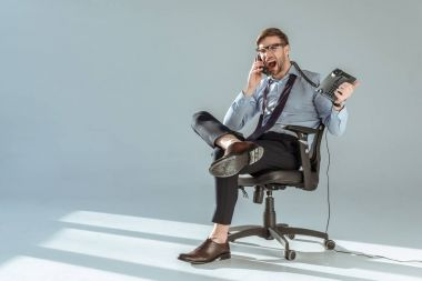 Young annoyed businessman sitting on chair and screaming while talking on phone