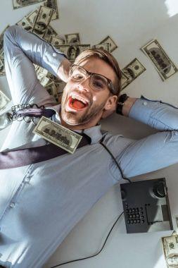 Young rich successful businessman lying on dollar bills