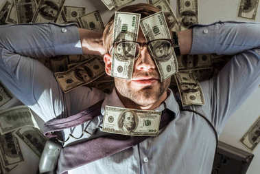 Young successful rich businessman lying on floor with dollar bills covering his face