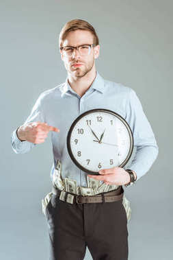 Thoughtful businessman pointing on clock isolated on grey