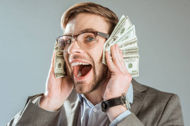 rich happy businessman holding dollar bills near his face isolated on grey