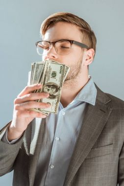 Young businessman kissing dollar bills isolated on grey