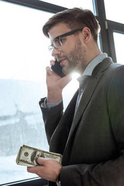 Young confident businessman holding money and talking on the smartphone by the window