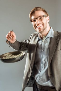 Young smiling businessman frying dollar bills in pan isolated on grey