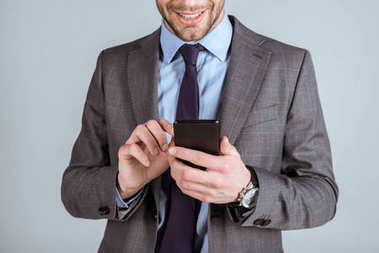 Young confident businessman using smartphone isolated on grey
