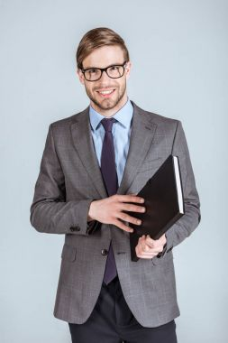 Young smiling businessman opening notebook isolated on grey