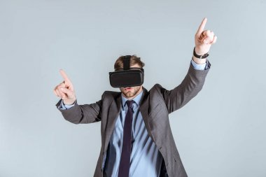 Young businessman in vr headset pointing up isolated on grey