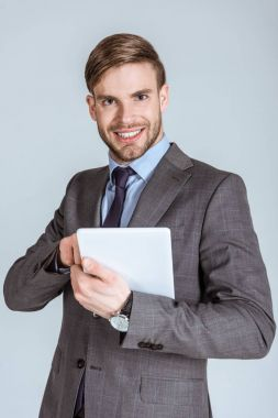 Young confident businessman using digital tablet isolated on grey
