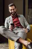 Fotografia uomo bello allegro in occhiali utilizzano smartphone