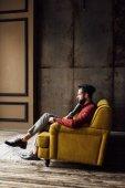 Photo fashionable elegant man sitting on yellow sofa