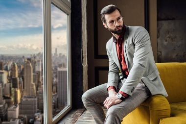 stylish man in suit posing at window with city view