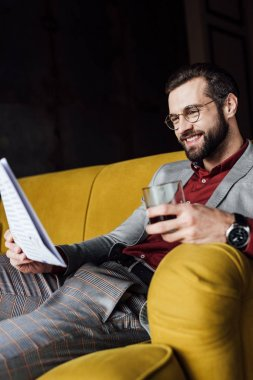 smiling man holding glass of cognac and reading newspaper