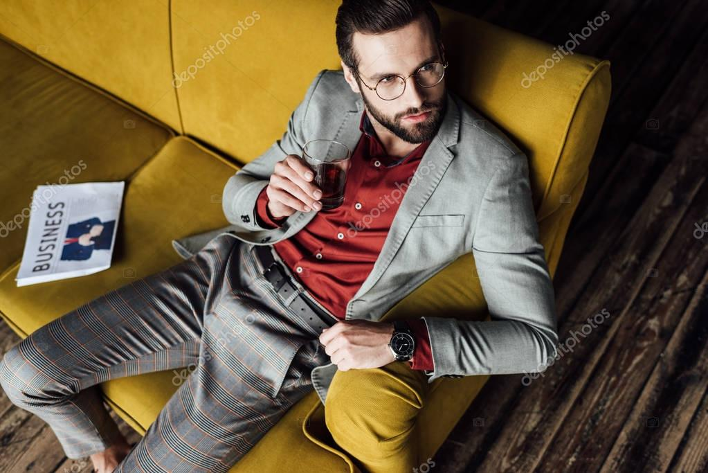 elegant man holding glass of whiskey and sitting on sofa with newspaper