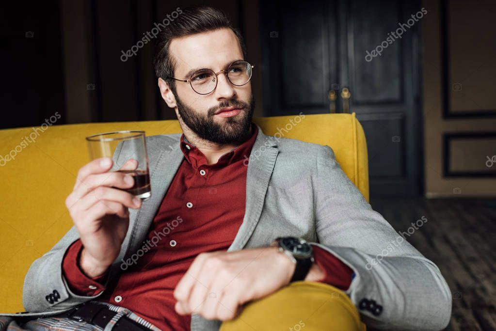 stylish bearded man holding glass of whiskey