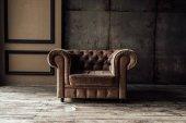 Fotografie Luxusní hnědé křeslo a popelník na podlahu v interiéru podkroví