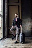 Fotografie elegante Geschäftsmann im Anzug posiert auf Hocker mit Gepäck