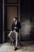 Fotografie schöner modischer Geschäftsmann im Anzug posiert auf einem Hocker im Loft-Interieur