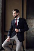 Fotografie schöner stylischer Geschäftsmann im Anzug posiert auf einem Hocker im Loft-Interieur