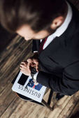 Photo overhead view of businessman looking at wristwatch while standing at stool with business newspaper and smartphone